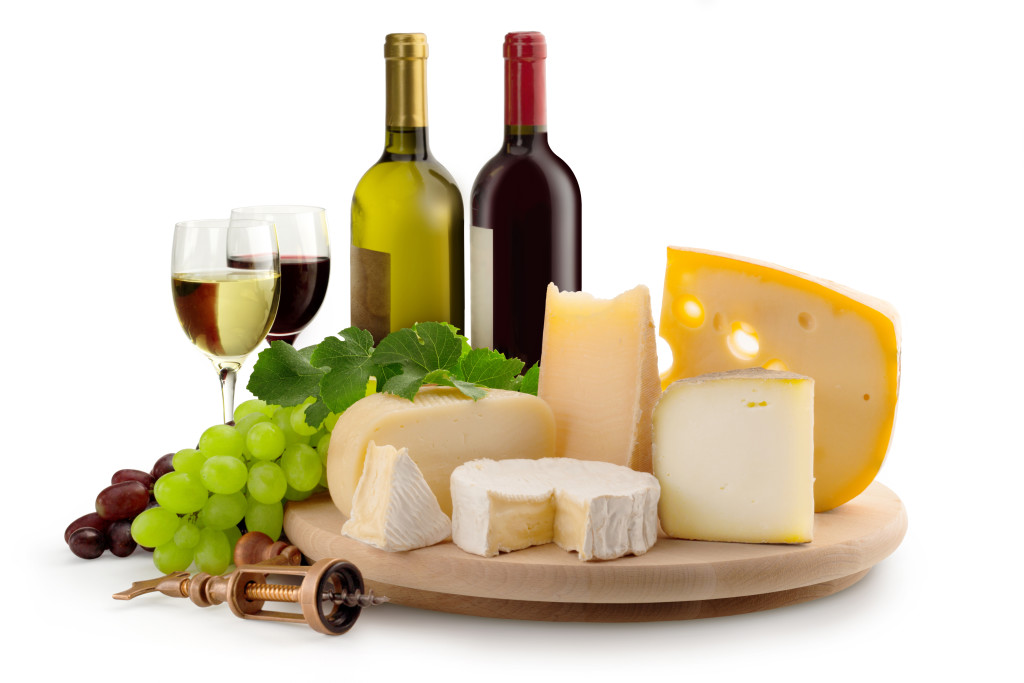 cheeseboard, grapes, wineglasses and wine bottles